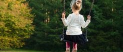 young girl on swing with back to camera